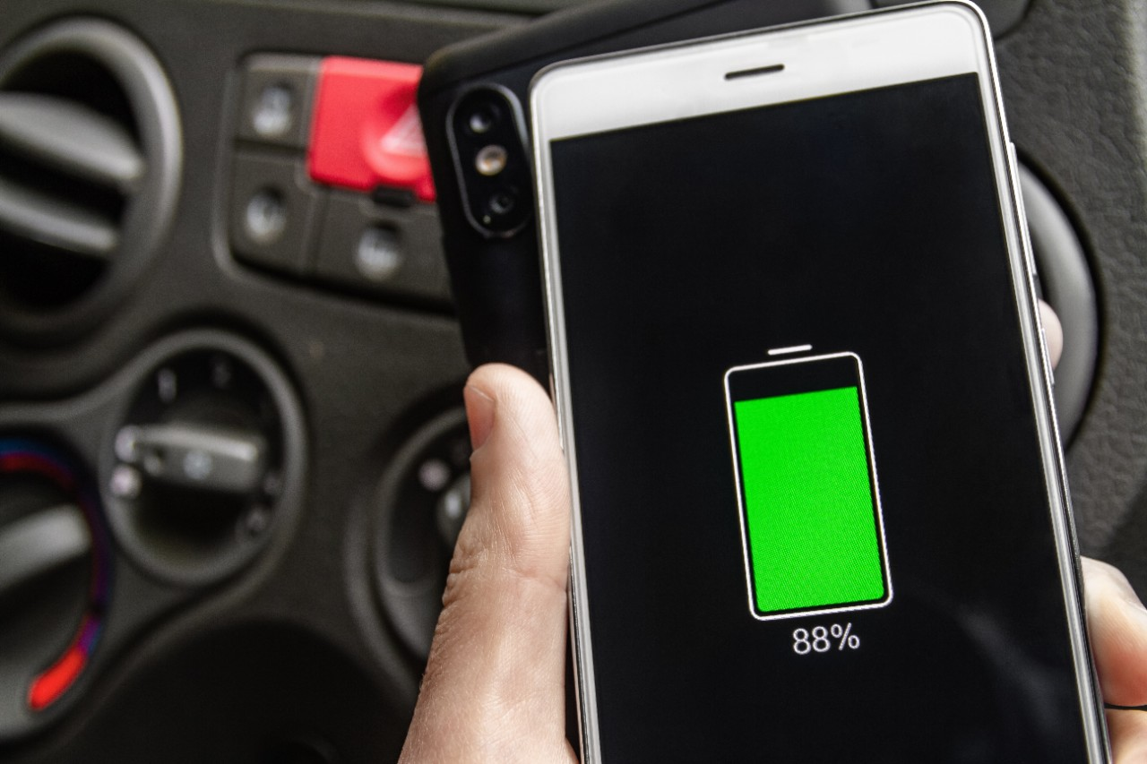 Phone battery wireless charge sharing technology. Wireless charge sharing smartphone in the car in rainy weather