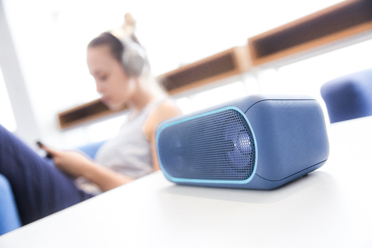 Wireless speaker with girl with headphones in a background; Shutterstock ID 751656148