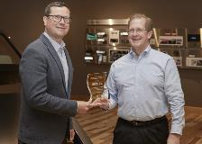 Joe Thomsen (right), vice president of Microchip's MCU16 business unit, presents Microchip's milestone award to Steve Downing (left), CEO of Gentex, on Wednesday, May 15, 2019.